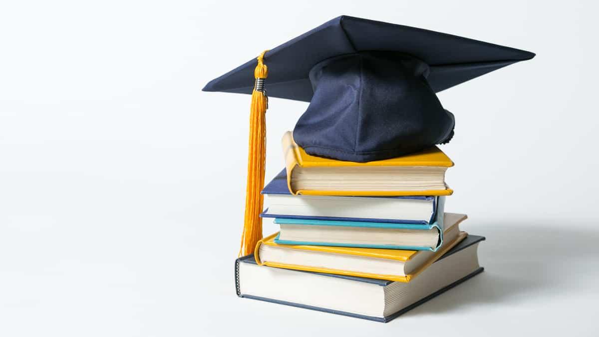 graduation cap on books